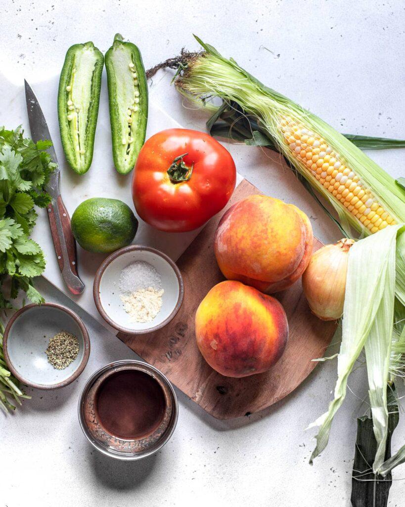fresh peach salsa ingredients: peaches, tomato, corn, jalapeño, onion, lime cilantro, hot sauce, spices