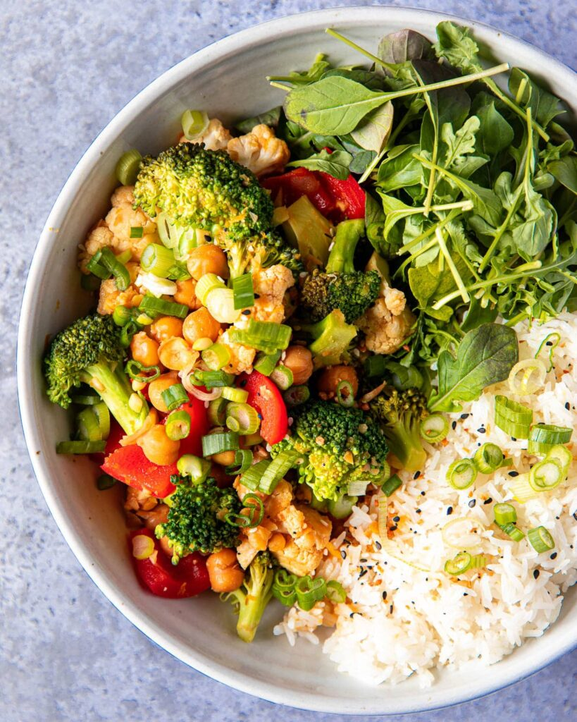 Orange chickpeas and vegetables with rice and greens