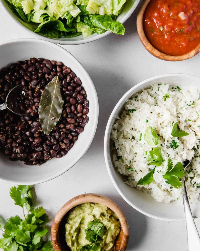 vegetarian burrito bowl ingredients, lettuce, salsa, beans, rice, guacamole