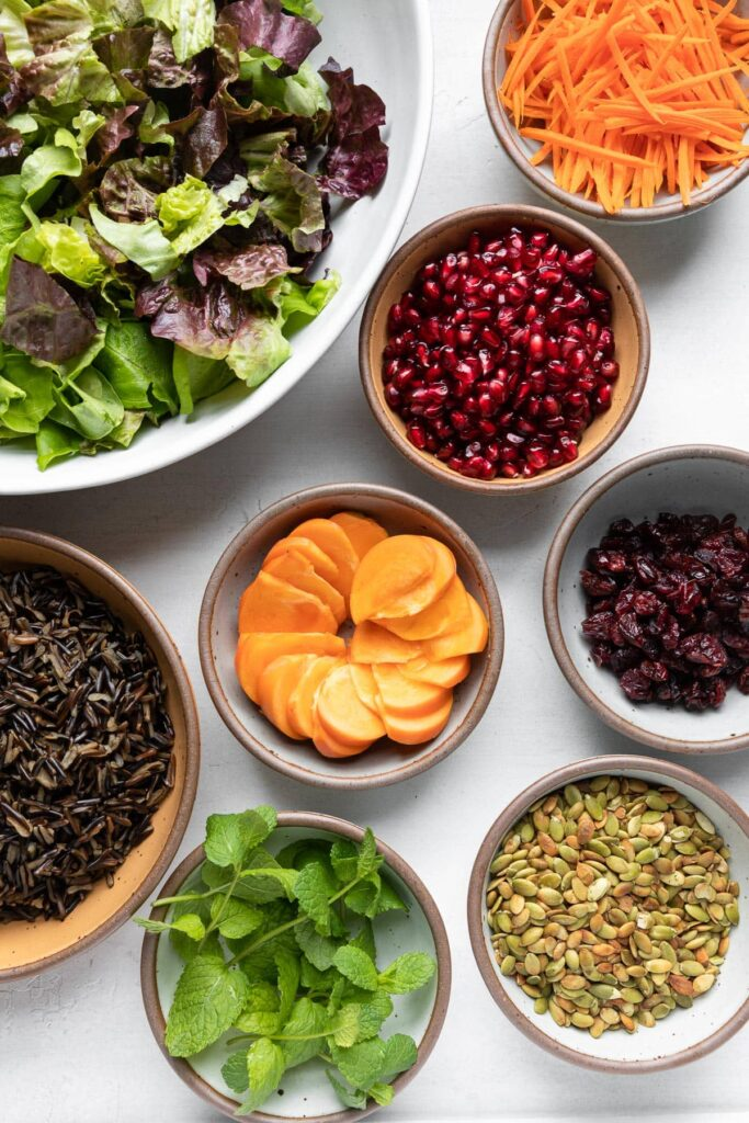 Wild Rice Holiday Salad ingredients: lettuce, carrots, pomegranate, persimmon, dried cranberries, wild rice, pumpkin seeds, mint