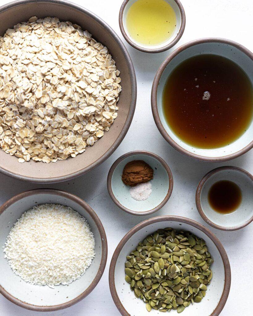 Easy Healthy Granola Recipe ingredients; oats, avocado oil, maple syrup, coconut pepitas, vanilla, cinnamon, salt