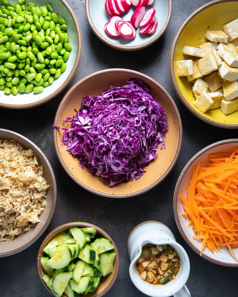 poke bowl ingredients, edamame, radishes, red cabbage. tofu, carrots, rice, cucumbers, sauce